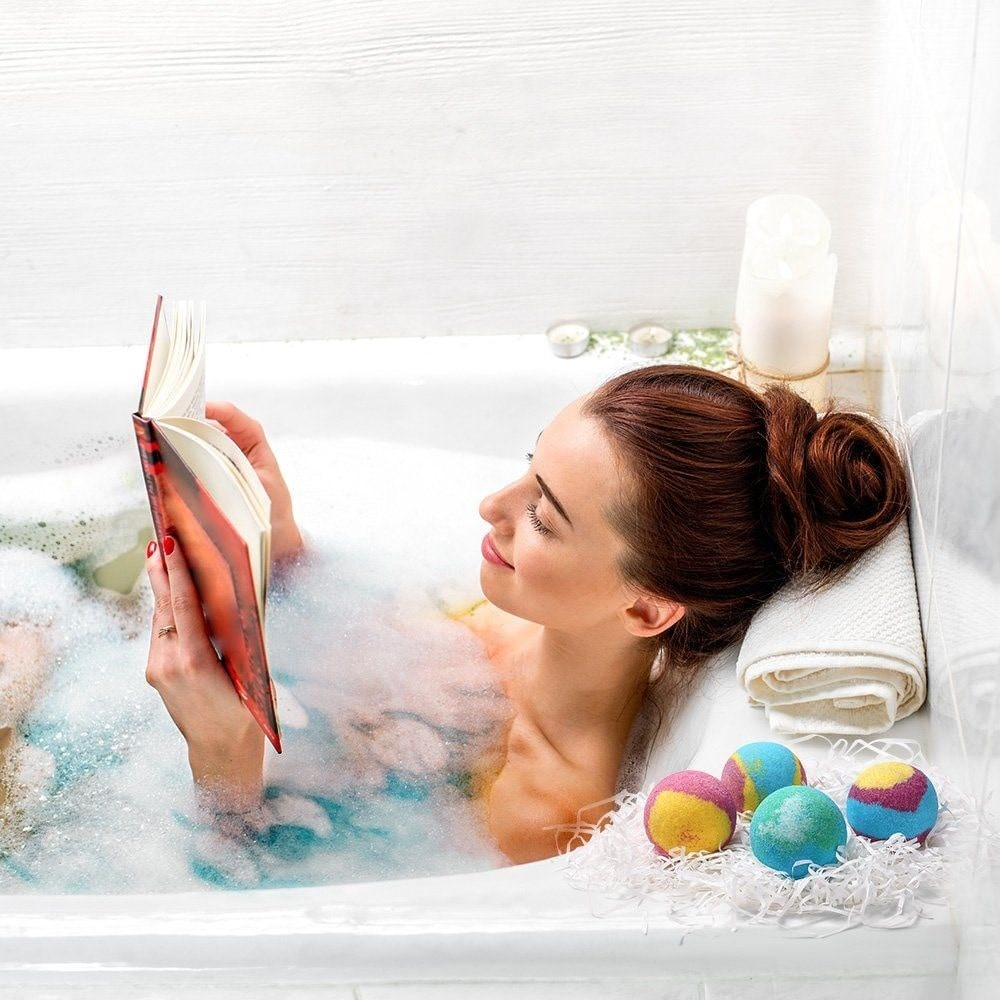 woman lying in bath tub, reading.