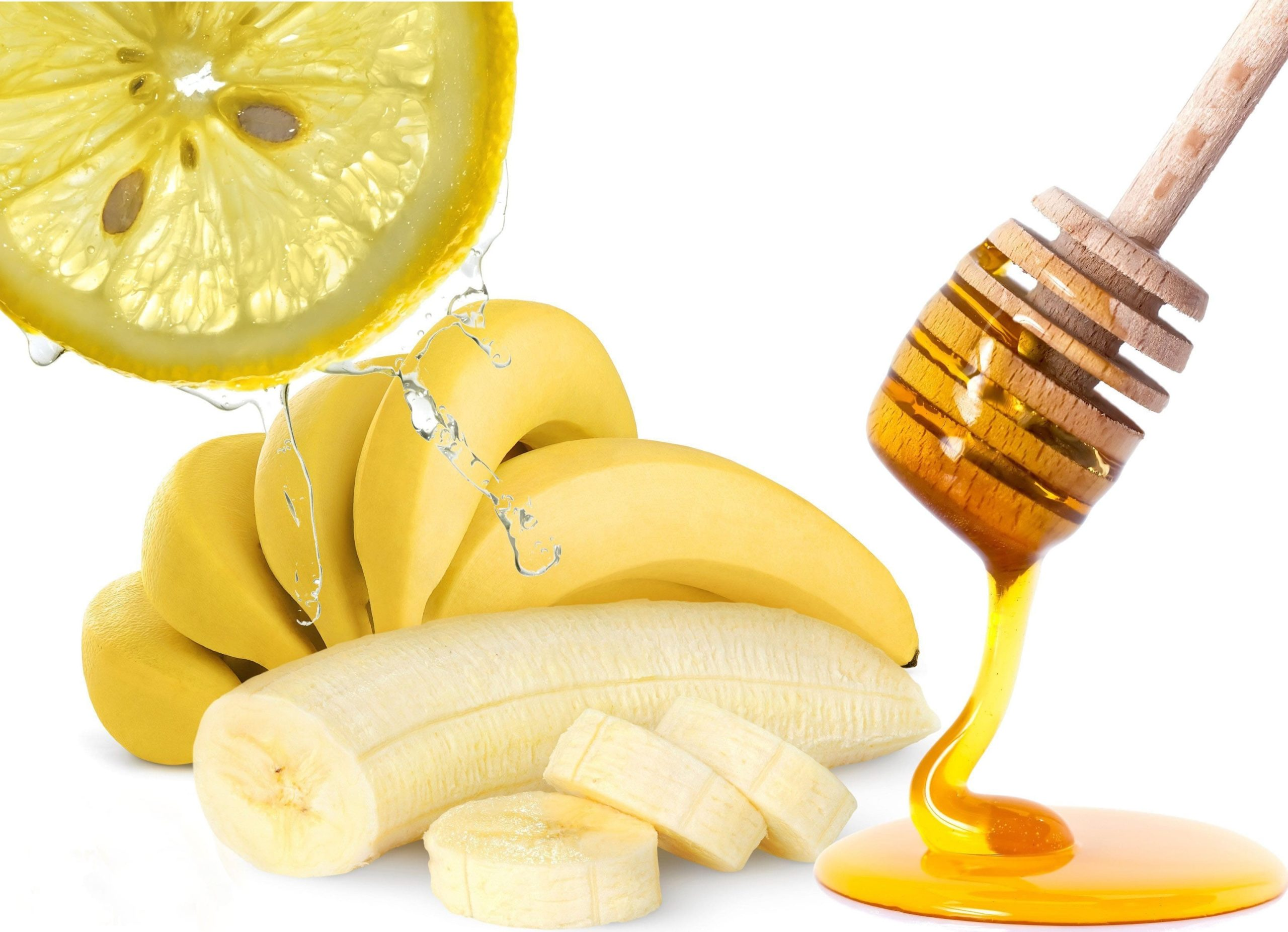 a banana sliced next to a spoonful of honey and a slice of lemon.