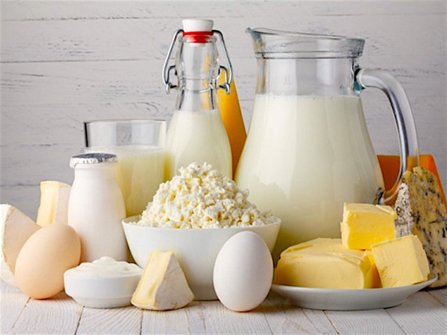 a selection of dairy products with a white brick background.