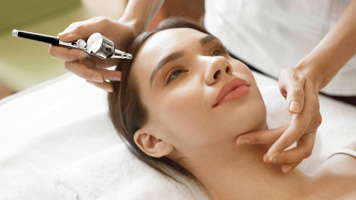 beauty therapist performing an oxygen facial on a client.