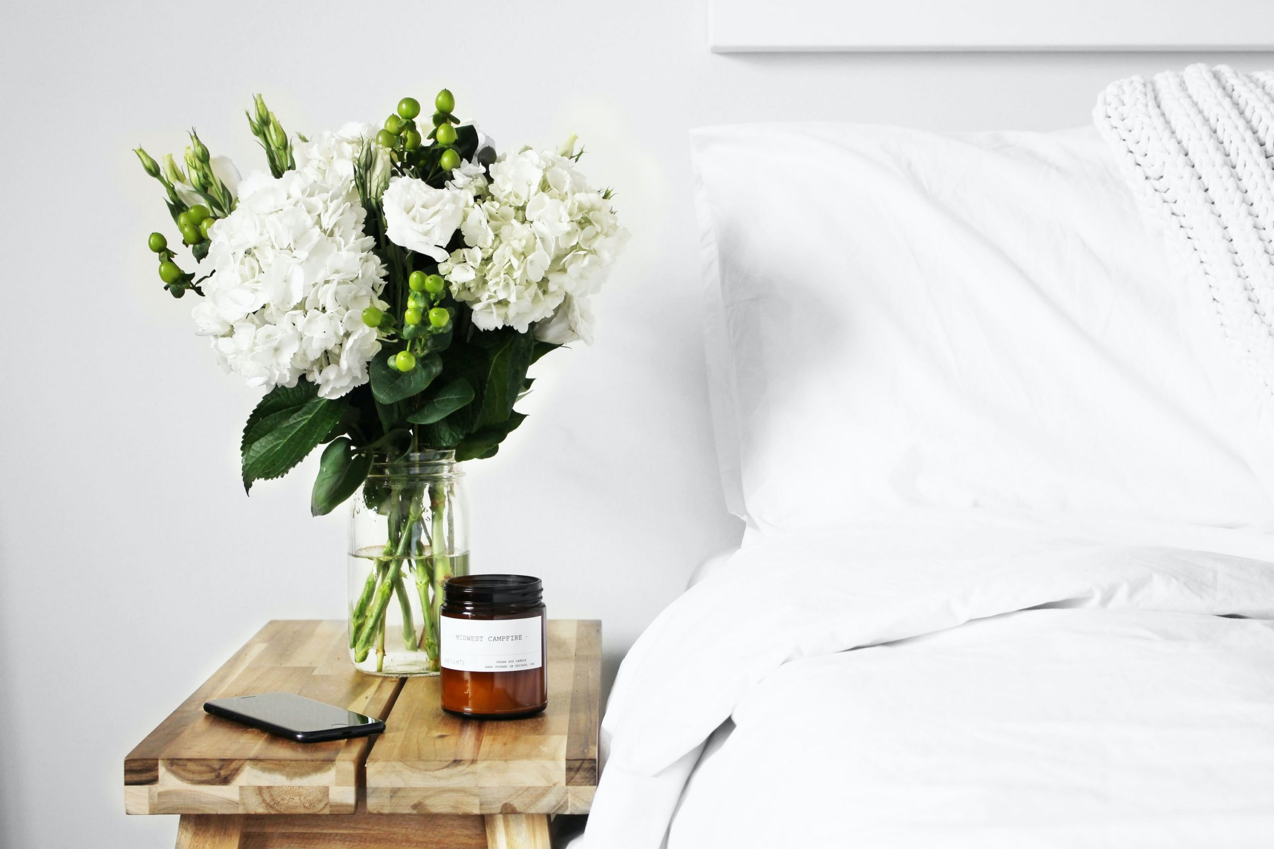 bed, with white pillow, next to a vase of flowers and a candle on a wooden table.