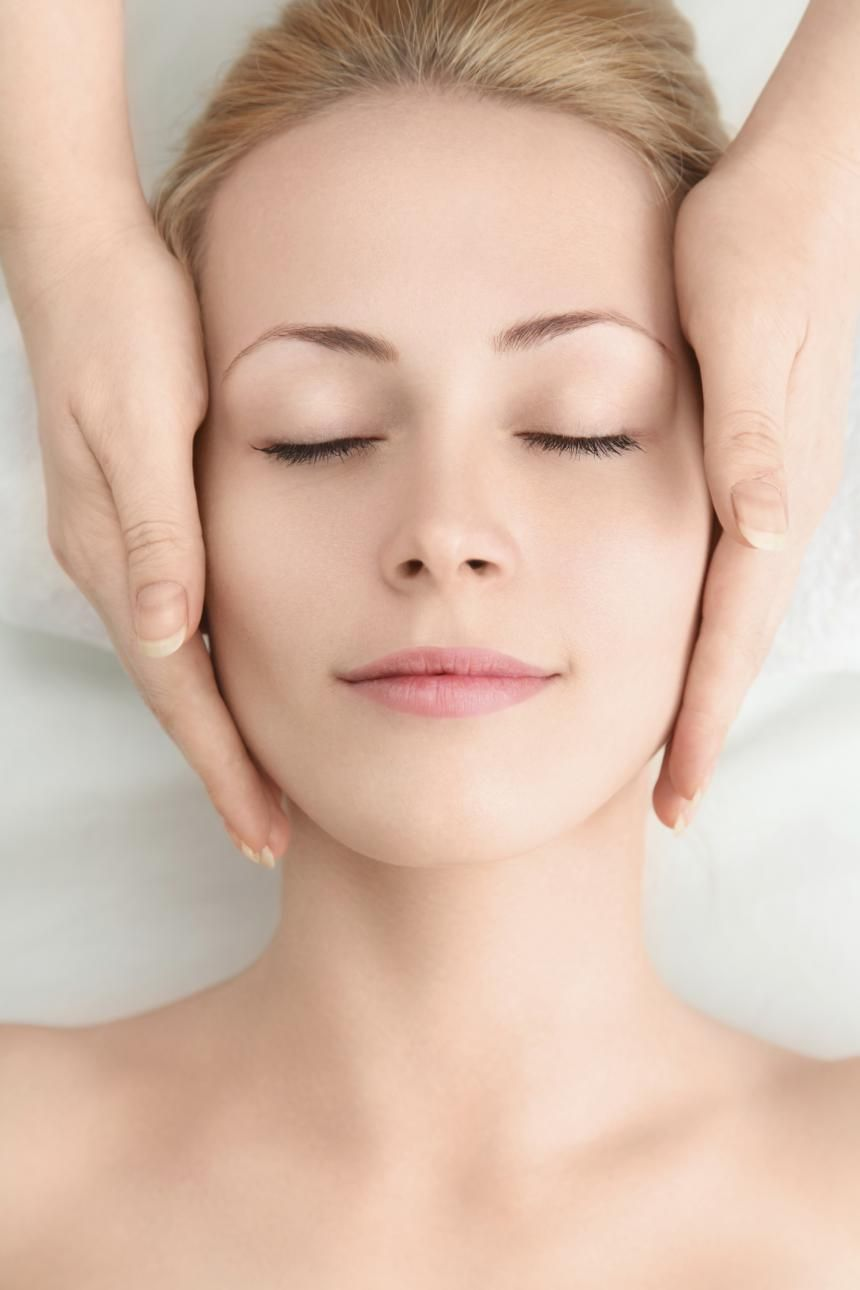 two hands holding either side of womans head, lying on a white spa bed.