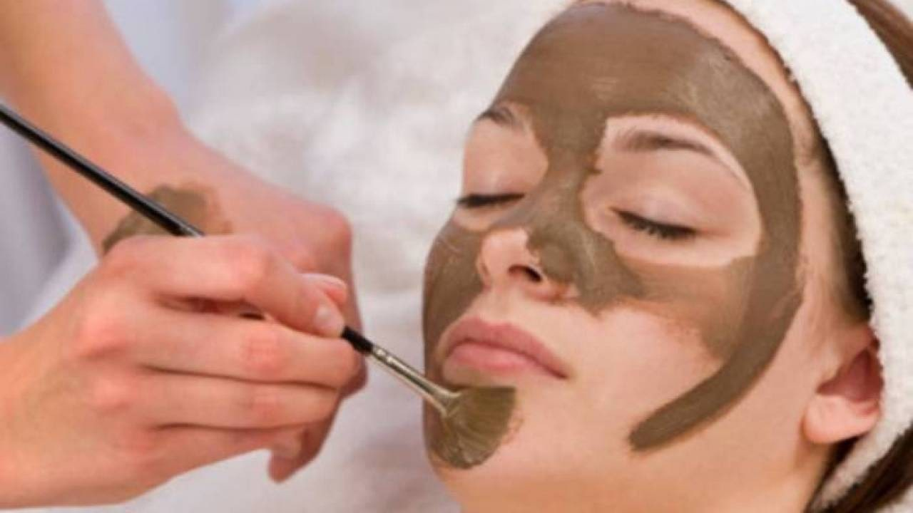 woman having cocoa applied to her skin by brush.