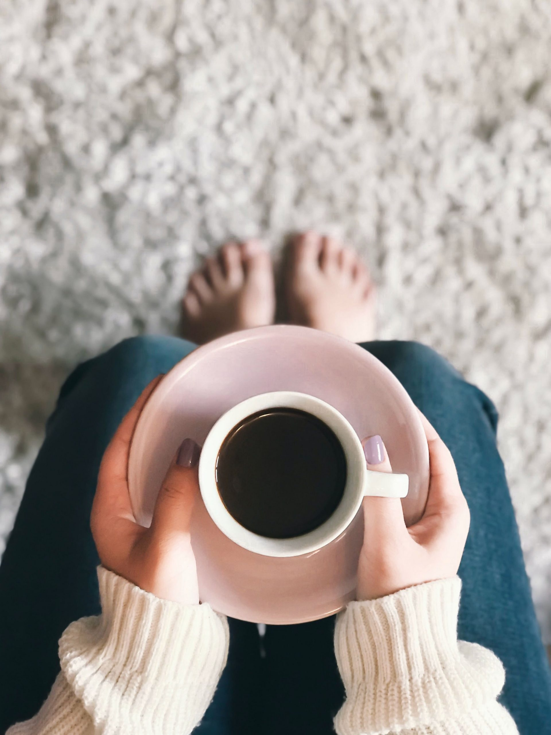 woman holding a mug filled with coffee, on their lap, say on a fluffy rug.
