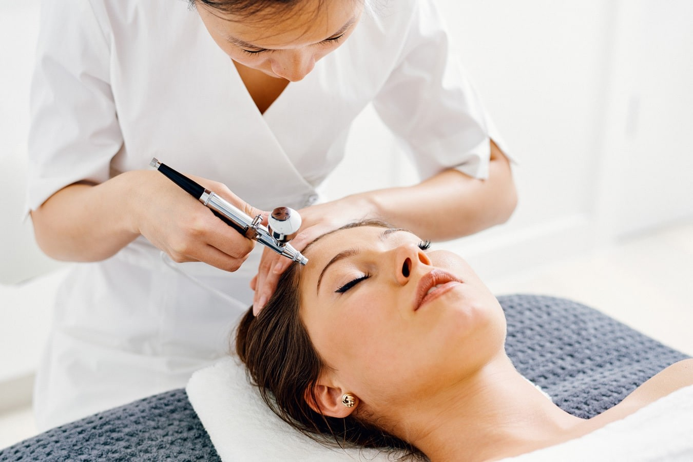 woman lay on beauty bed having oxygen facial therapy.