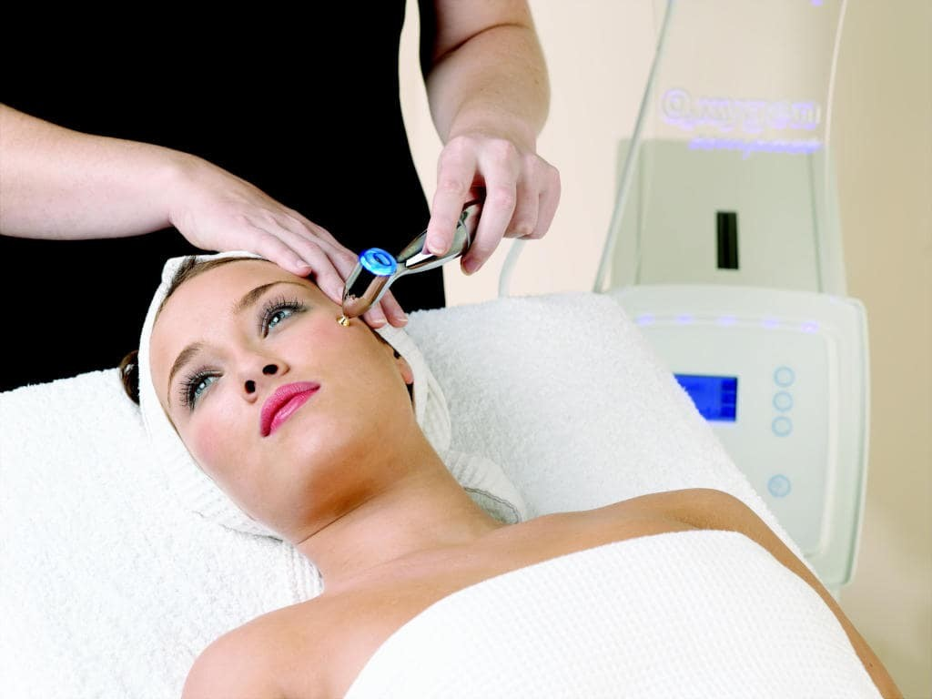 woman lying down having oxygen facial therapy.