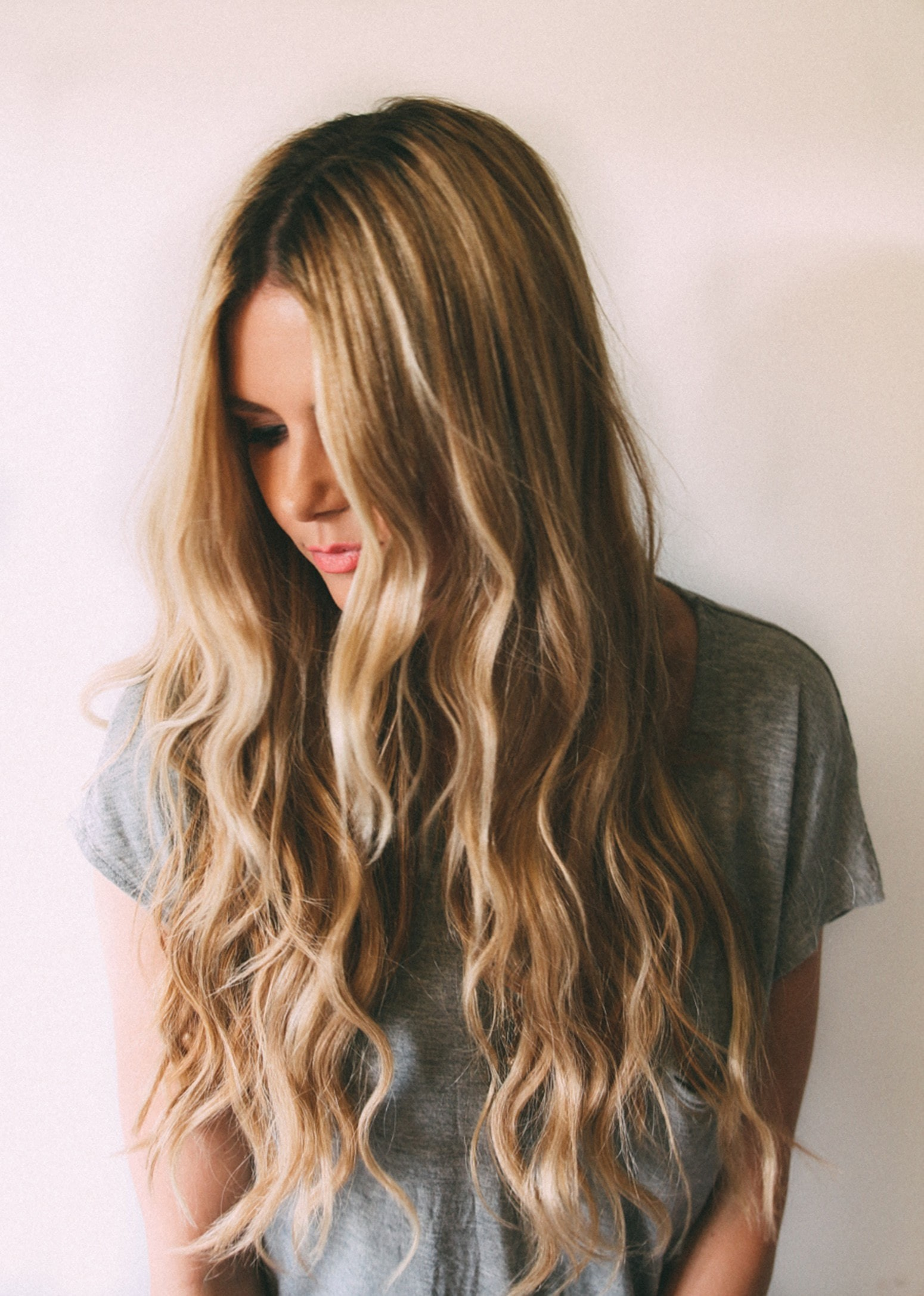 woman pictured with long blonde beach waves in her hair.
