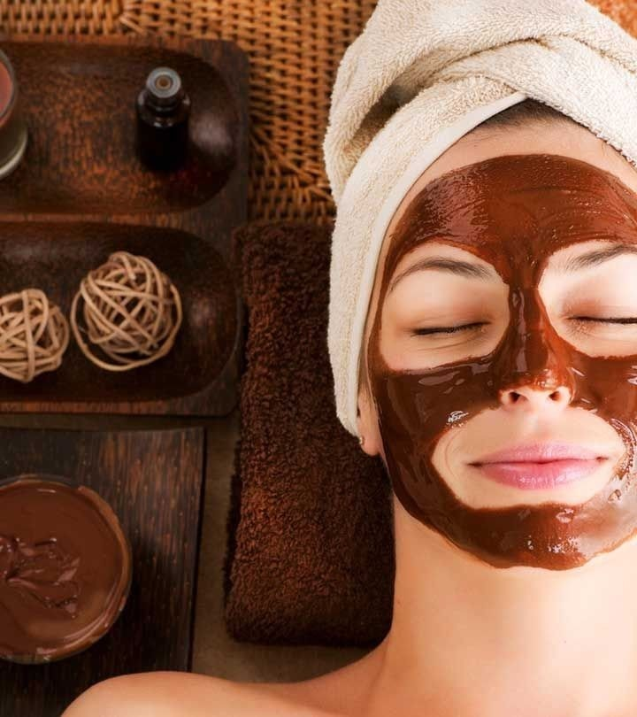 woman relaxing wearing a cocoa facial mask, with her hair in a towel.
