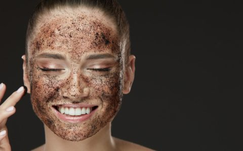 woman smiling with her face covered with powdered chocolate/cocoa.