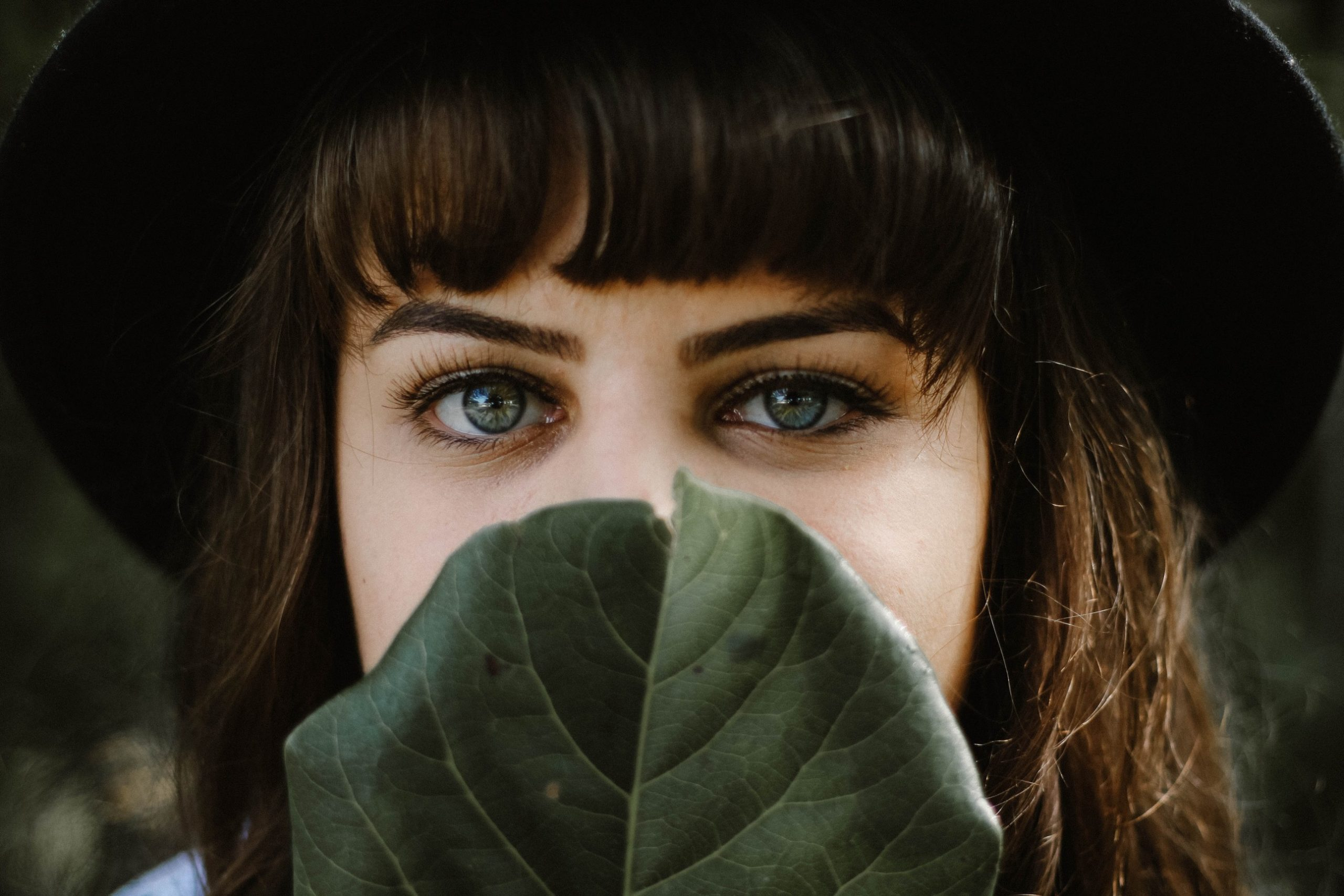 causes of acne can be fringes: woman with a curled fringe holding a leaf over her face.
