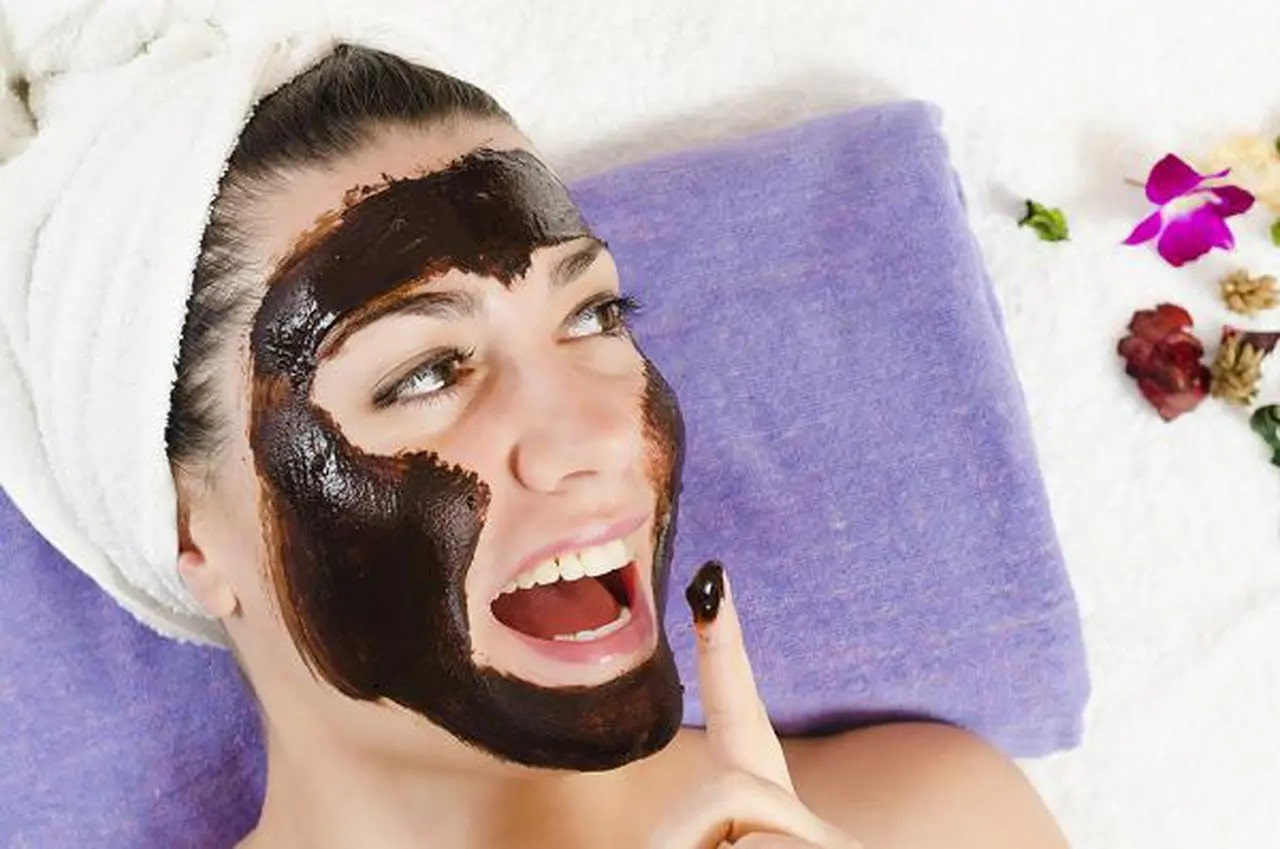 woman with cocoa mask on her face, leaning on a purple towel.