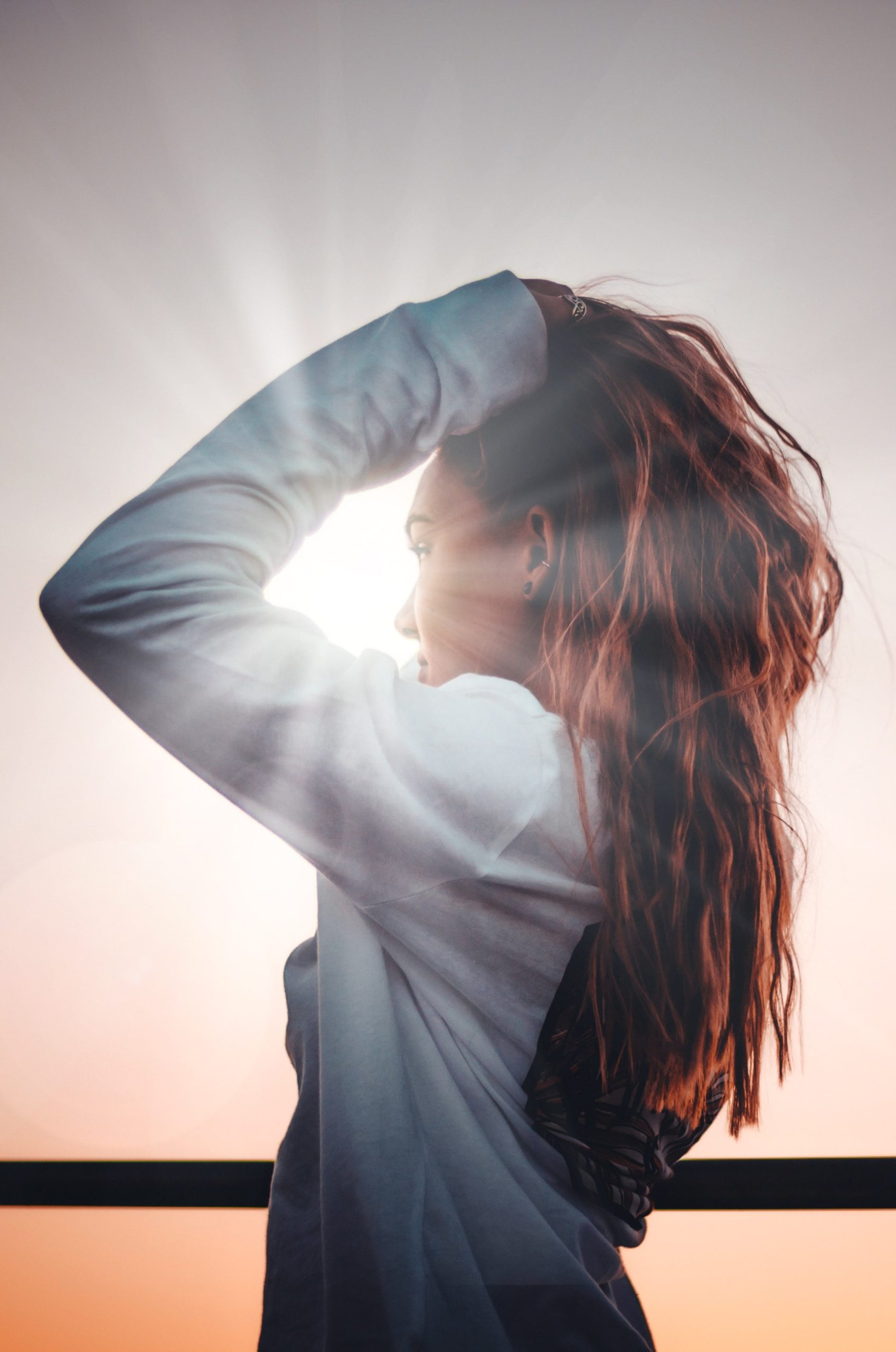 woman with long curly hair facing into the sun.