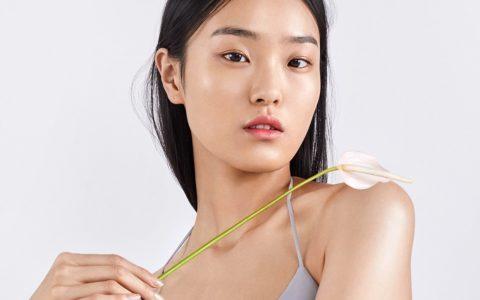 korean model posing holding a flower over her shoulder.