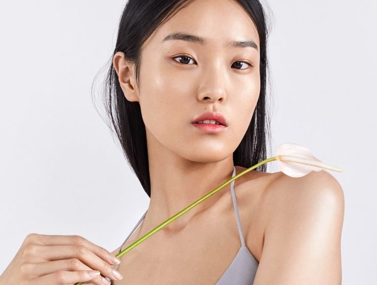 korean model posing holding a flower over her shoulder.