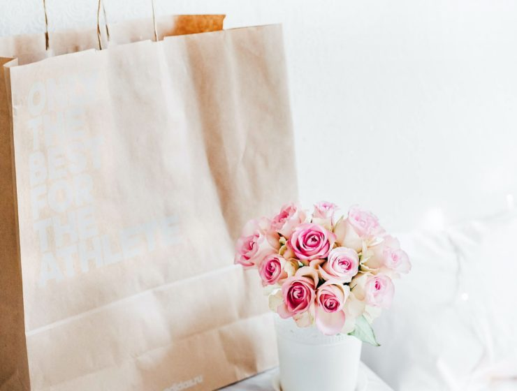 vase of roses sat next to a brown paper shopping bag.