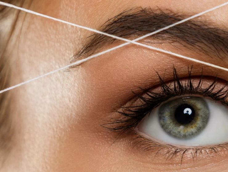 close up of a woman have facial threading around her eyebrows.