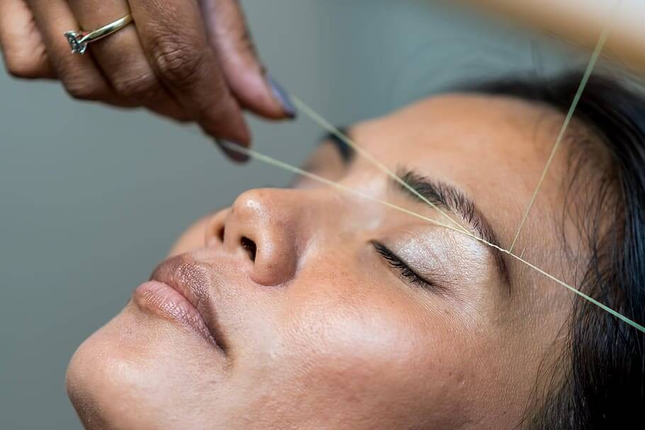 woman having facial threading on her eyebrows.
