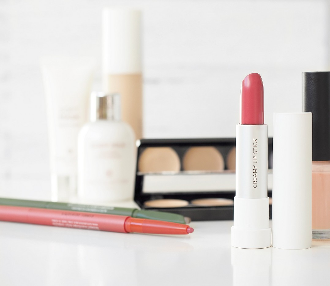 makeup essentials, including lipstick, lip liner and foundation, laid on a glossy white desk.