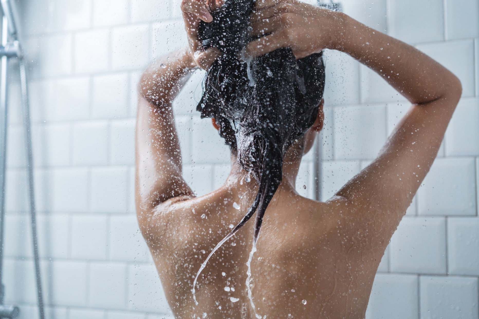 the back of someones back and head in the shower, washing their hair, with a tiled white background.