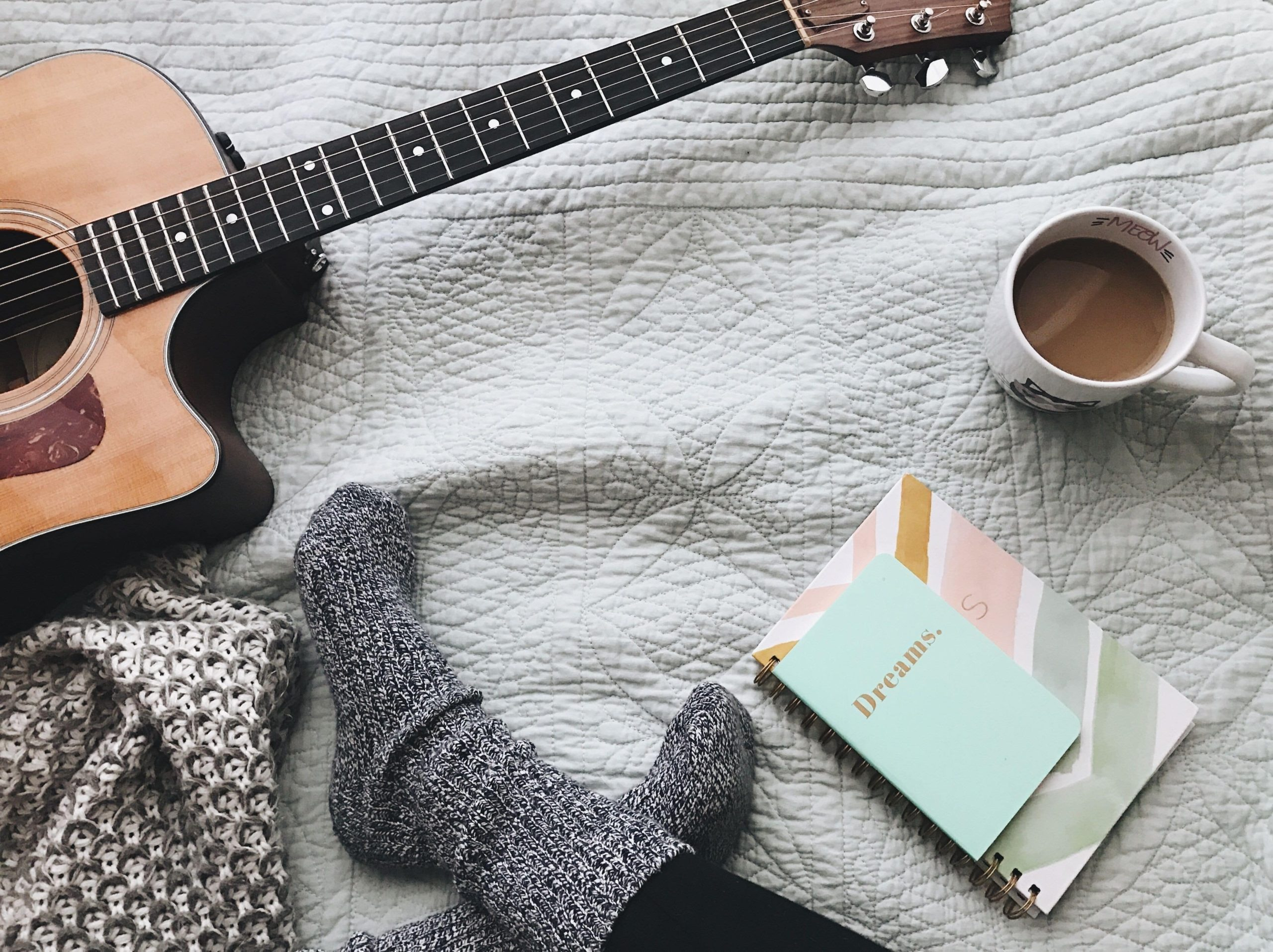 a persons' sock covered feet sat with a guitar, mug of coffee and a notepad.