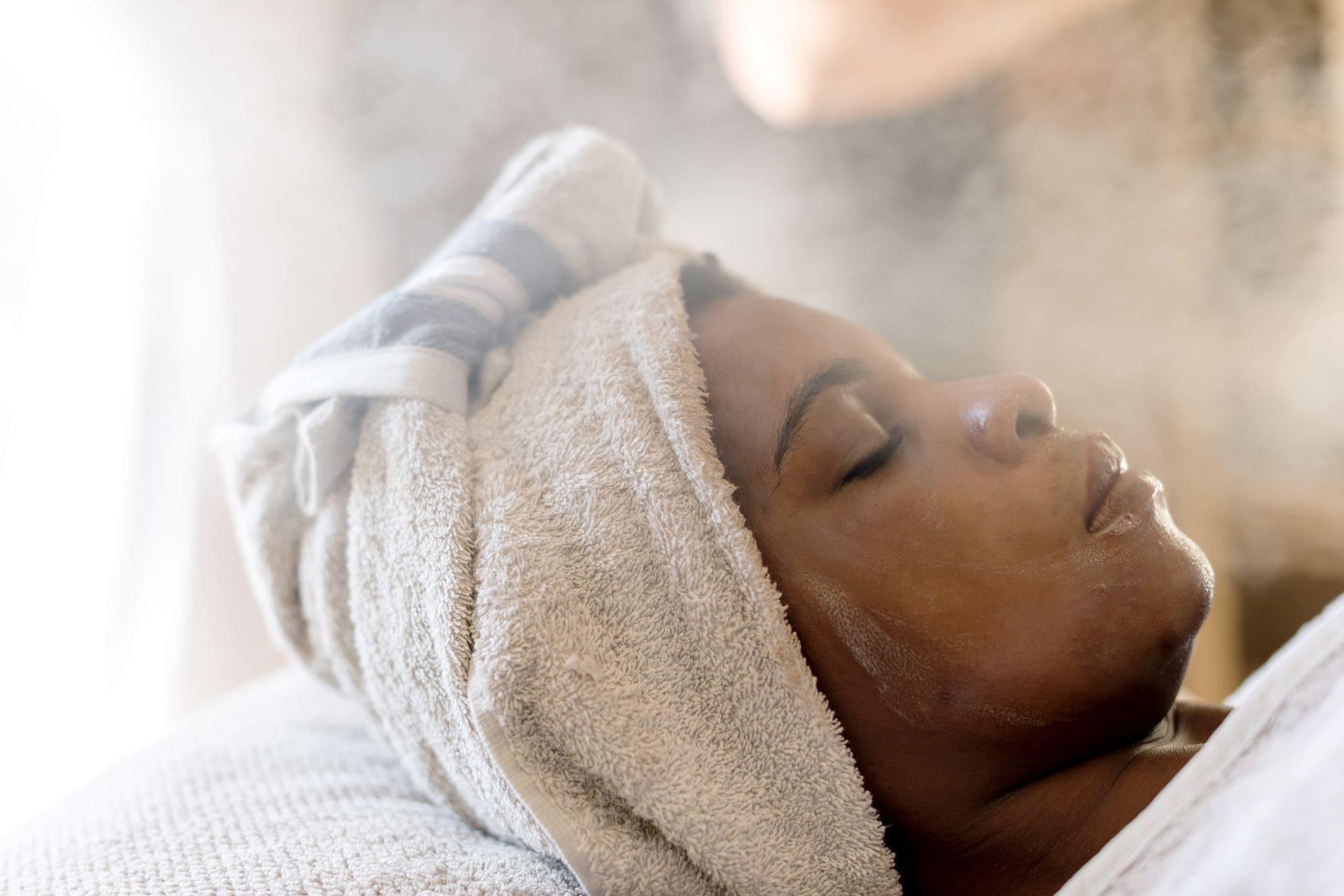 a woman lying in a spa, having a facial steam.