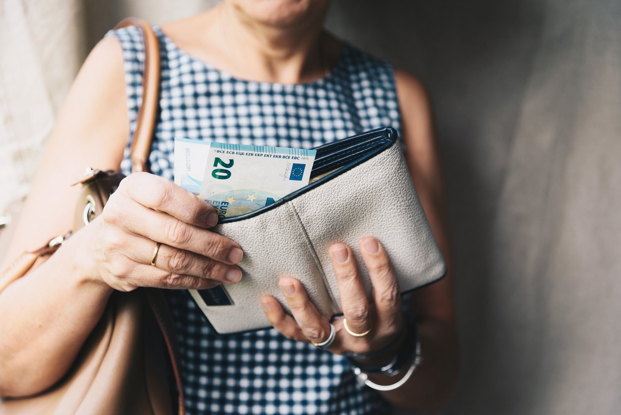 buying techniques: close up of a woman holding an open purse, showing the money inside.