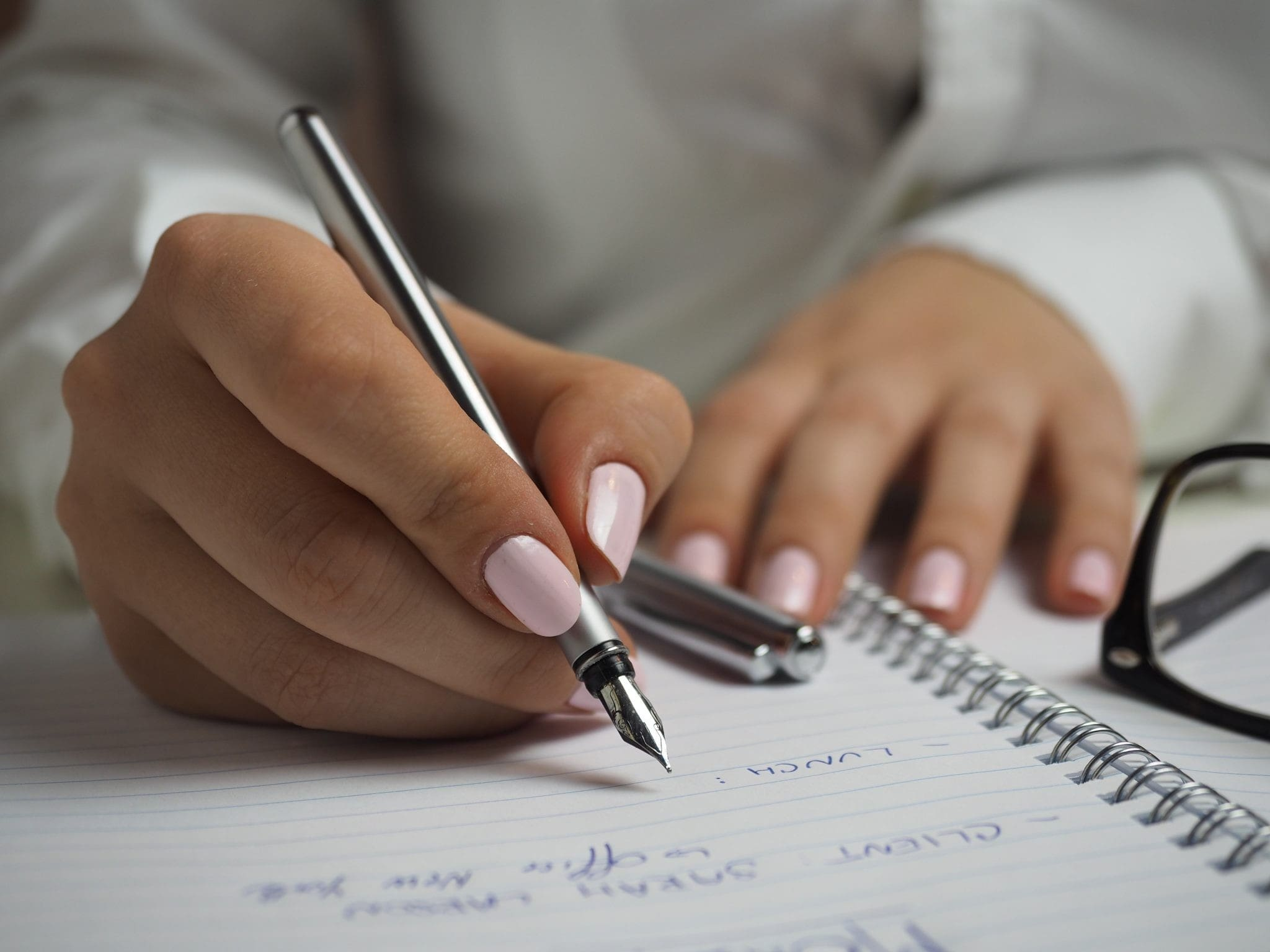 buying techniques: a woman, close up on her hands, writing a list on a sheet of paper.