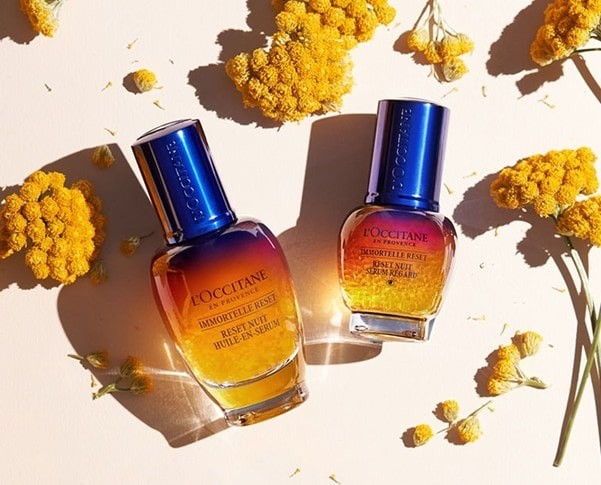 One of the Charitable Brands L'Occitane UK: two gradient shaded glass bottle products, lying next to flowers and petals.