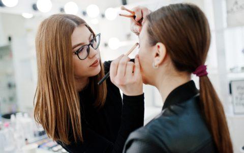 a makeup artist applying makeup to a client.