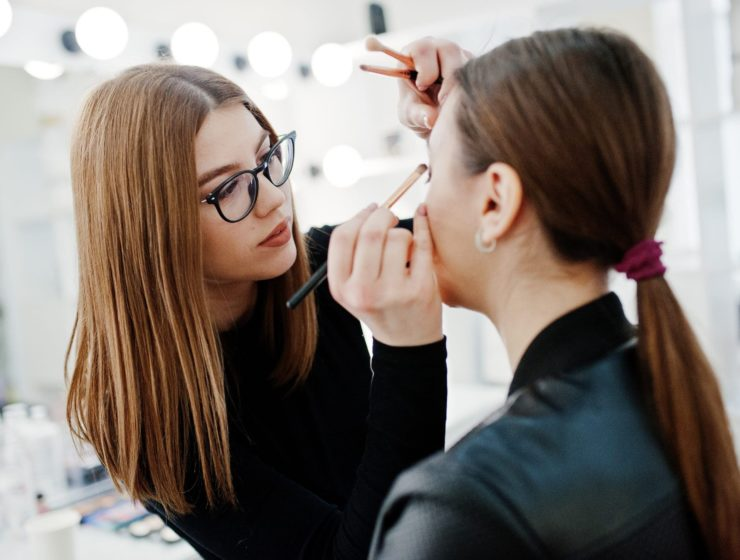 a makeup artist applying makeup to a client.