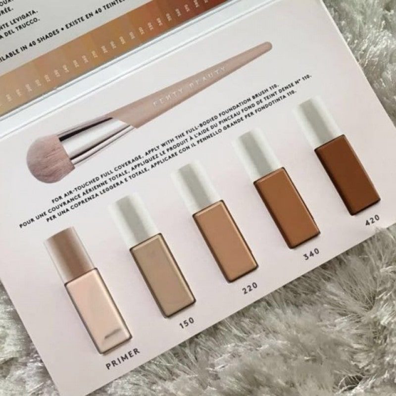 rihanna fenty makeup samples with mini brush, all contained in a white card leaflet upon a fluffy material.
