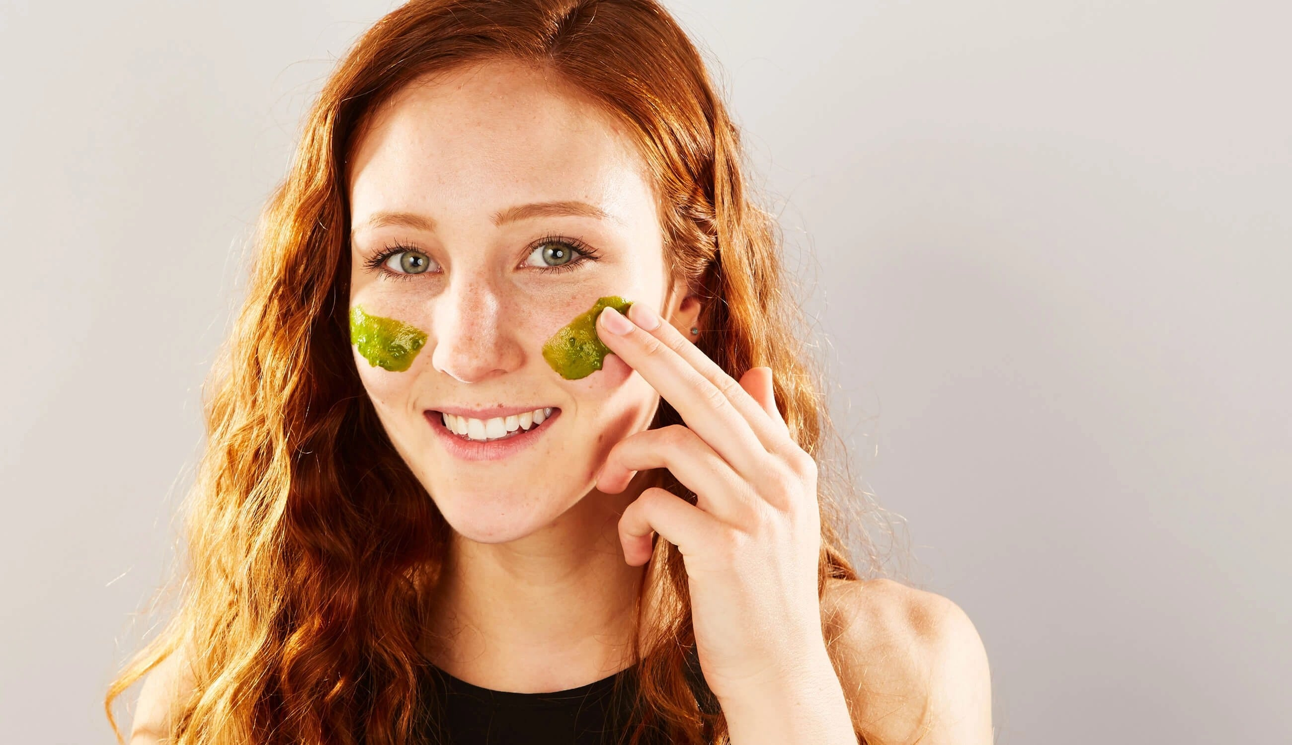 woman applying green paste to her cheeks.