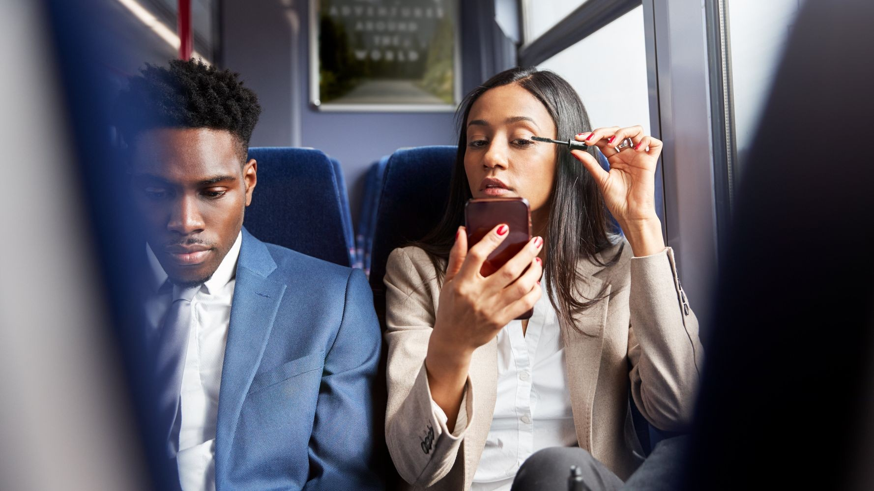 woman applying mascara whilst on the train, sat next to a fellow passenger.
