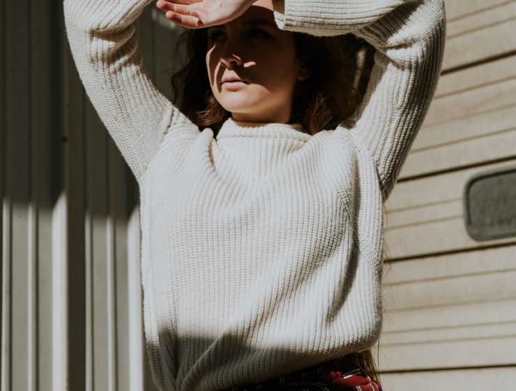 woman covering her face from sunshine, whilst wearing a cream jumper.