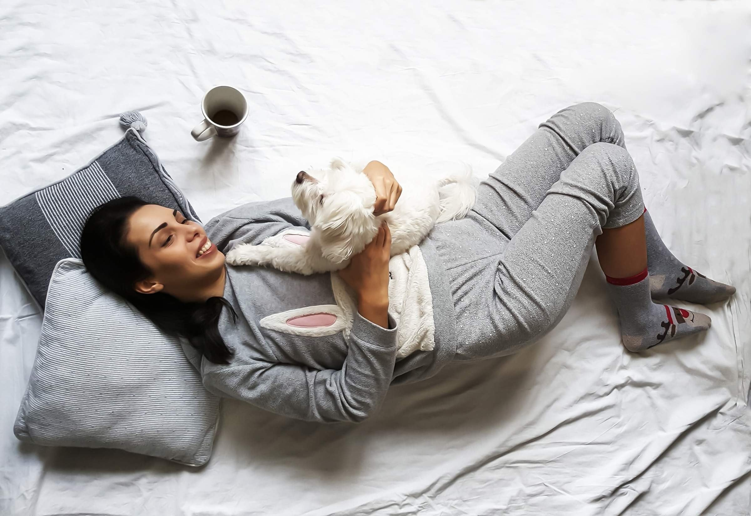 woman smiling whilst lying in bed, with her dog, and a mug of coffee.