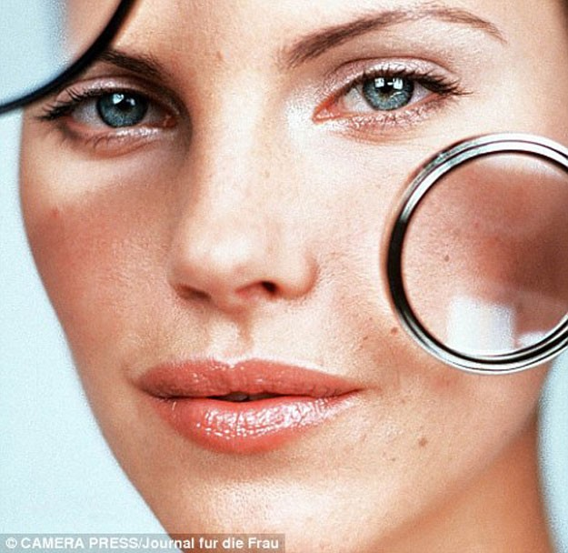 woman magnifying clogged pores on her face with magnifying glasses.