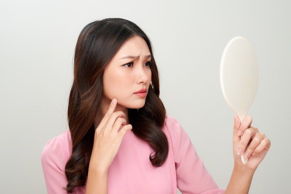 woman touching her face whilst looking into a handheld mirror