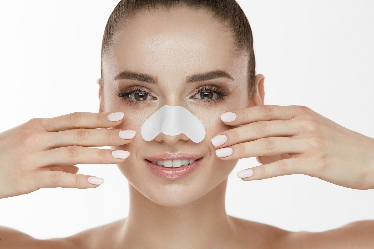 woman wearing a pore strip over her nose, for treating clogged pores.