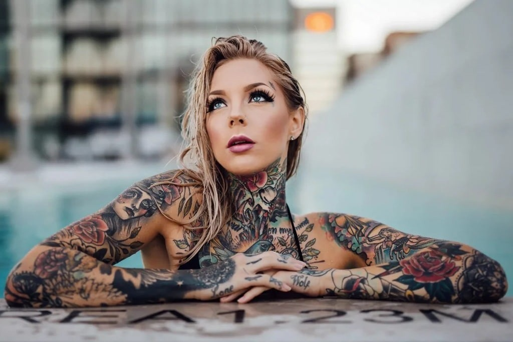 a woman covered in tattoos, leaning out of a pool.