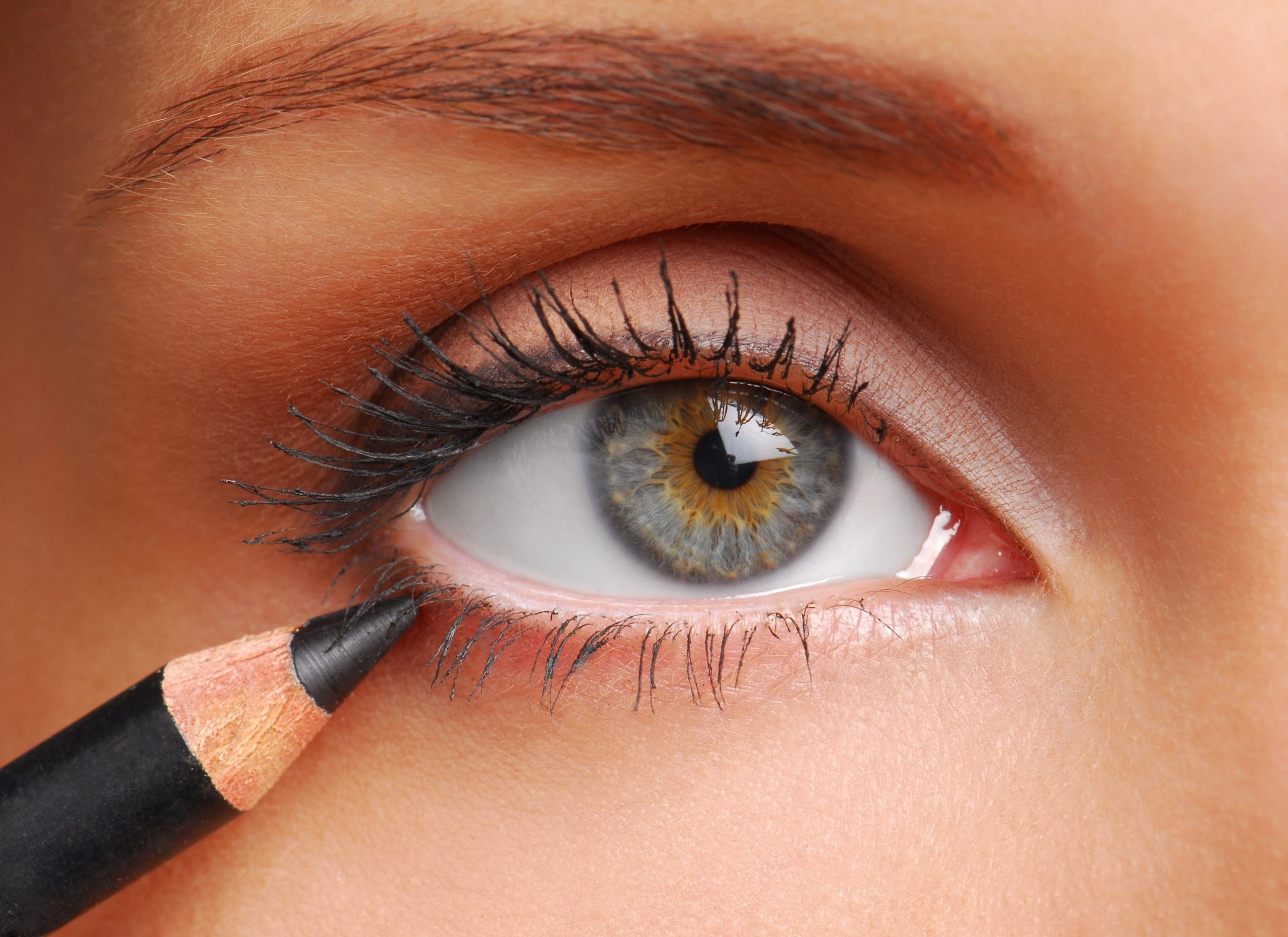 close up picture of a person applying eyeliner to their lower lash line.