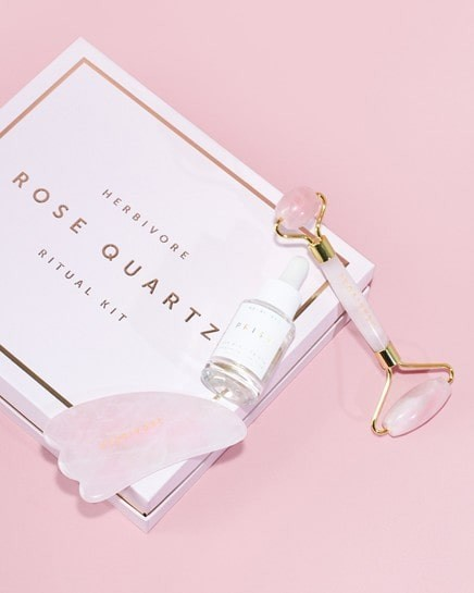 Spa Day Essential: Herbivore Rose Quartz Ritual Kit pictured on a pink background.