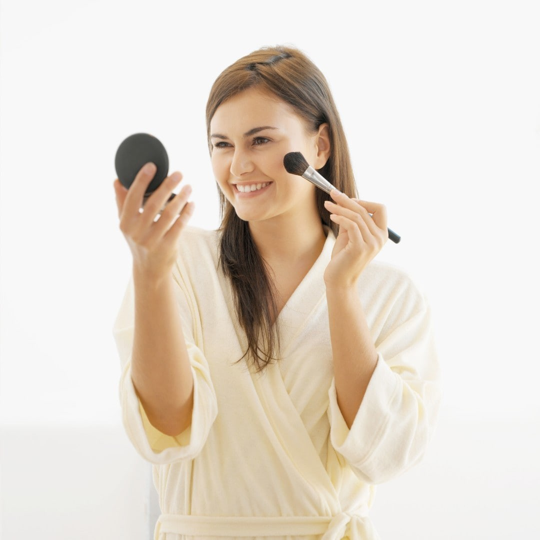 Be sure to avoid a makeup mistake when applying makeup to the cheek, pictured is a oman applying makeup to her cheeks using a mirror compact.