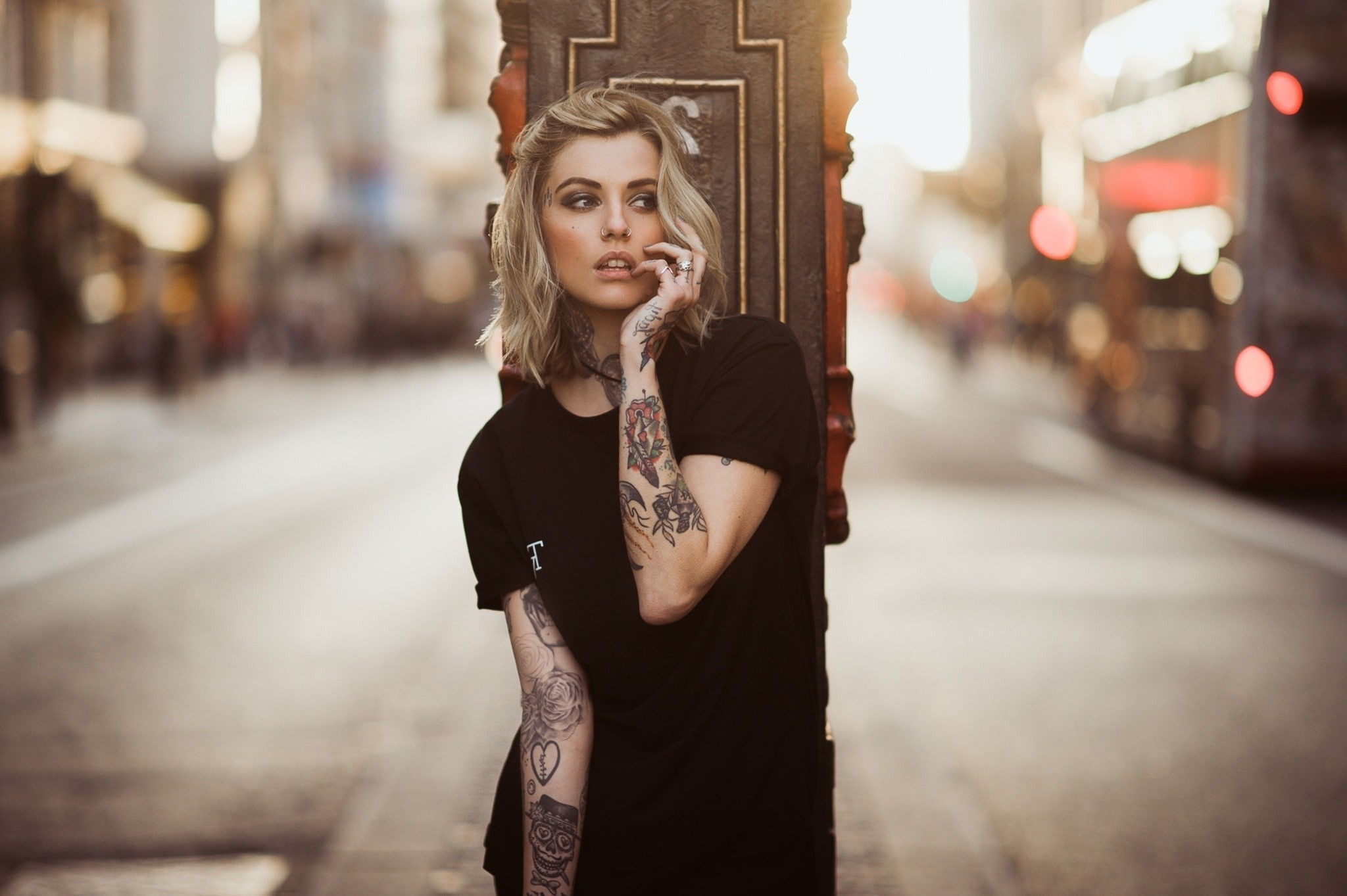 woman, with tattoos, leaning against a post.
