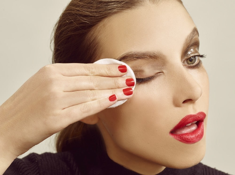 woman removing eye makeup, whilst wearing red lipstick, avoiding a makeup mistake.