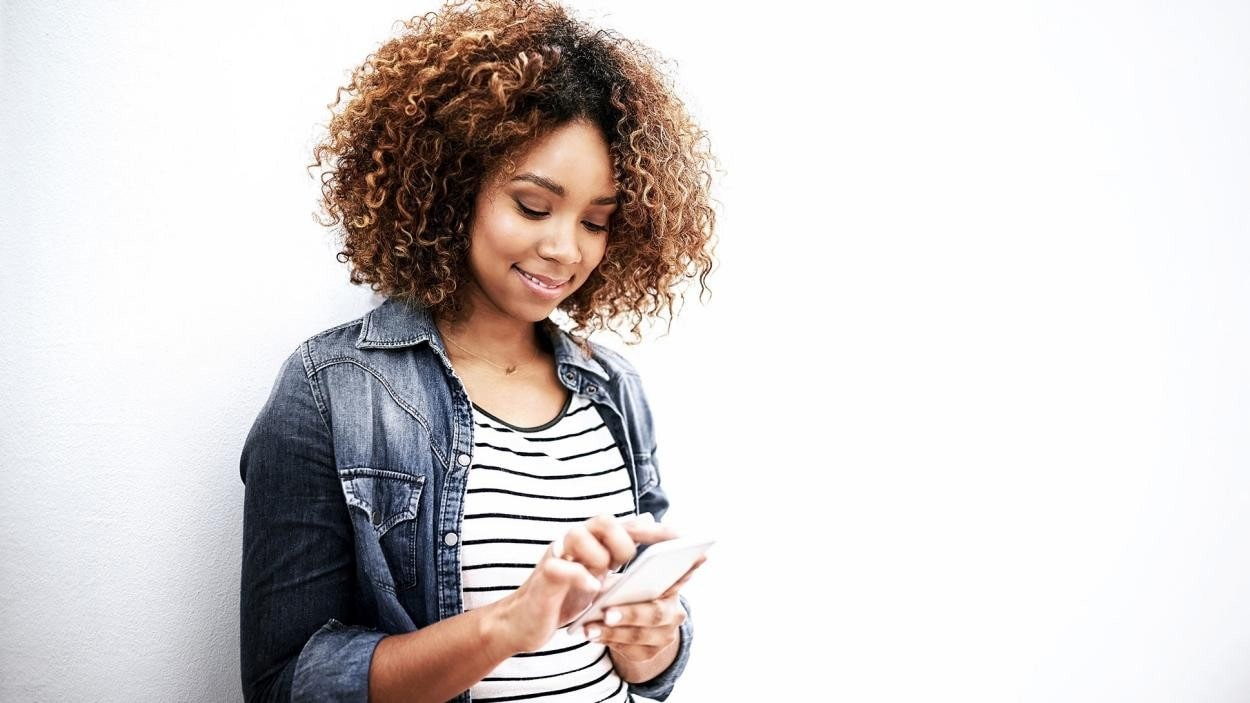 woman smiling whilst playing online on her mobile phone.