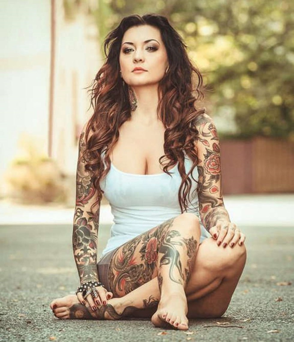 woman with full body tattoo sleeves sitting on a pavement wearing a white vest.