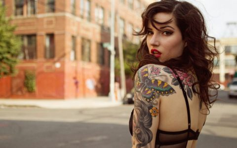 woman with tattoos posing over her shoulder, in the street.
