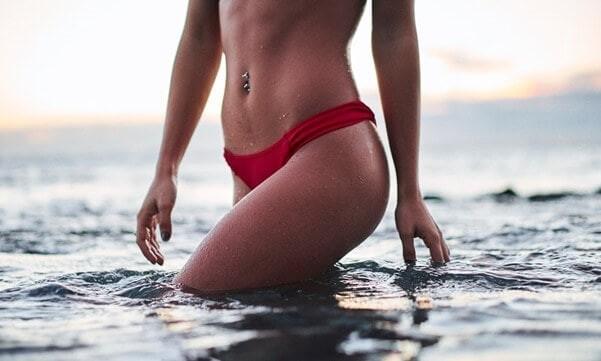 woman in water shown from waist down wearing bikini bottoms.