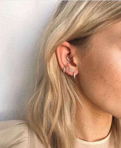 blonde haired perspn photographed from side, showing ear piercings.